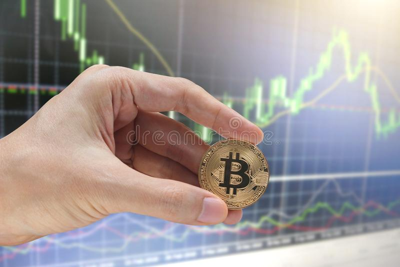 Hand holding the bitcoin with stock market or financial graph for financial investment concept.  stock image