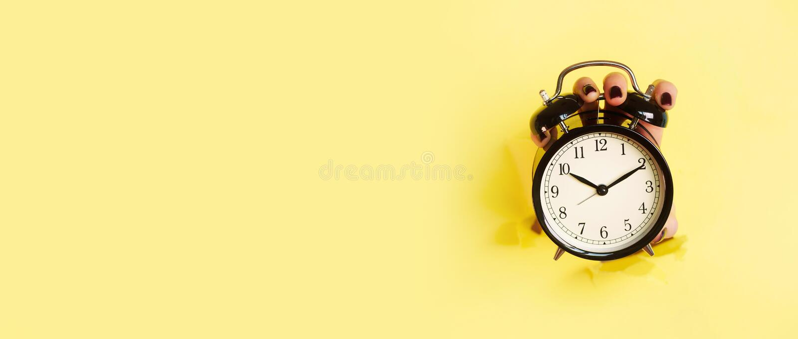Hand holding black alarm clock through hole in yellow paper background. Wake up alert concept. Morning routine. Banner with copy. Space royalty free stock image