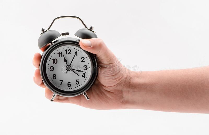Hand holding a black alarm clock on white background royalty free stock photos