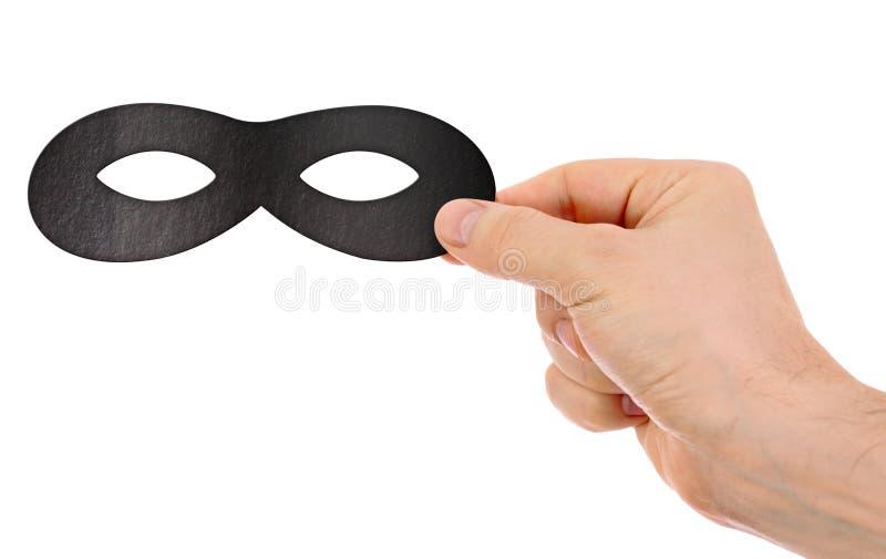 Hand holding black paper mask stock photo