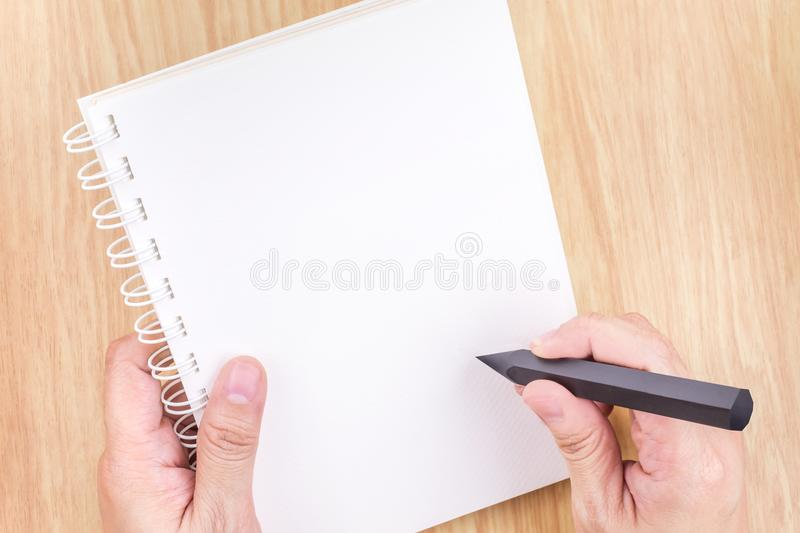 Hand holding black pencil and empty white open book above wood d. Esk ,Mock up template for adding your content royalty free stock image