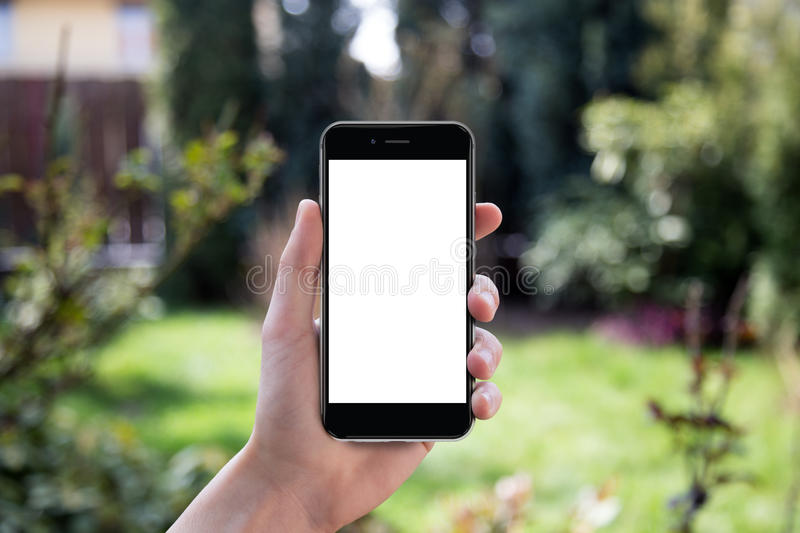 Hand holding black smartphone with blank screen. Hand holding black smartphone with blank screen against blurred garden background royalty free stock photos