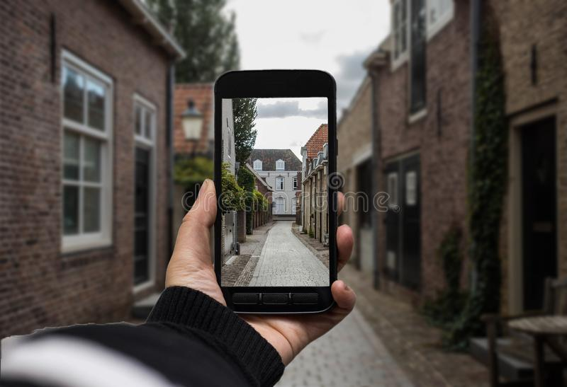 Hand holding the black smartphone with blank screen on background, making a photo of landscape. royalty free stock photos