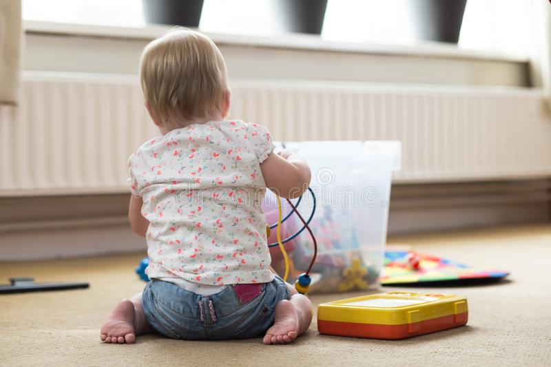 Baby playing alone with toys on a carpet on the floor at home royalty free stock photography