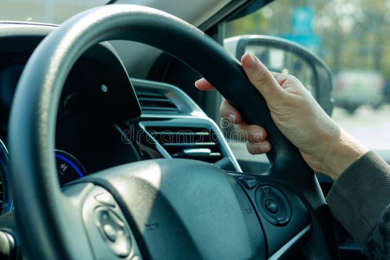 Hand holding on black steering wheel stock photography