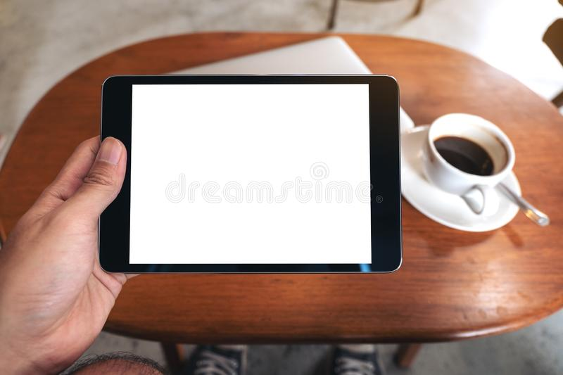 Hand holding black tablet pc with blank desktop white screen with laptop and coffee cup on wooden table stock photos