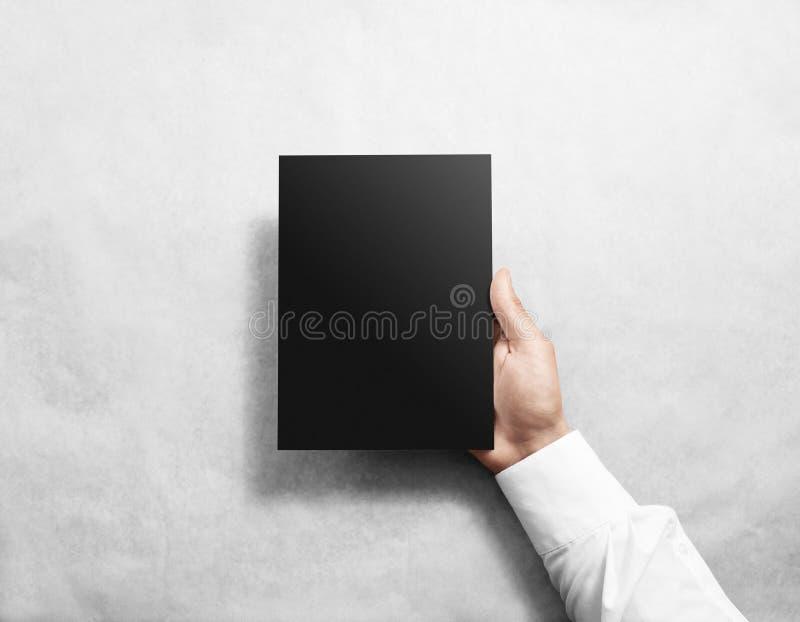 Hand holding blank black brochure booklet mockup. Leaflet mock up presentation. Pamphlet hold hand. Man show book offset paper. Sheet template. Booklet design royalty free stock photo