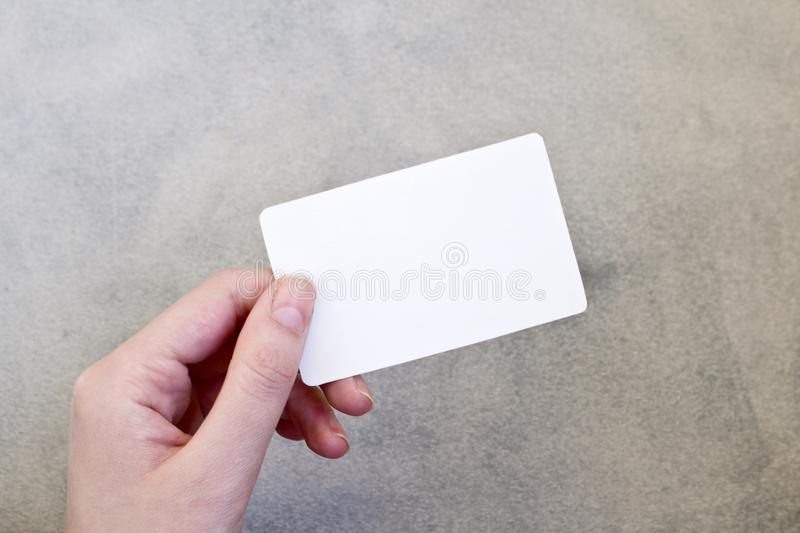 Hand holding a blank business card on gray background. royalty free stock photo