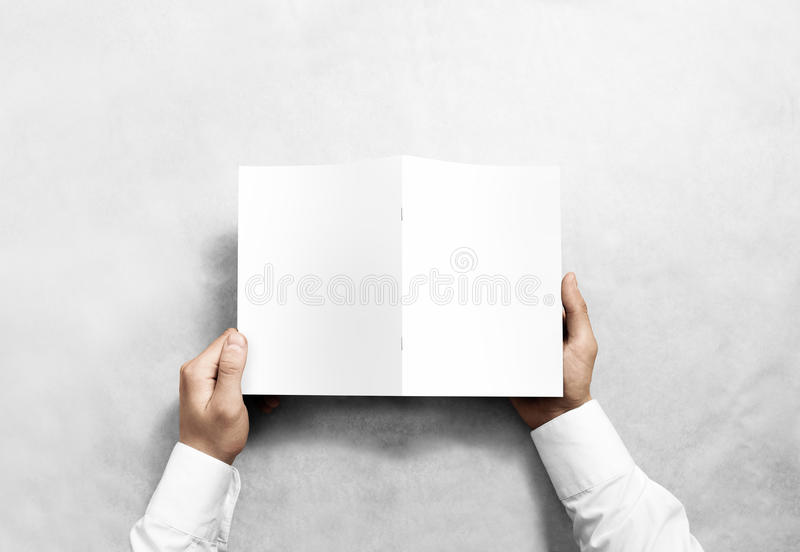 Hand holding blank white brochure mockup, back side view. royalty free stock photos