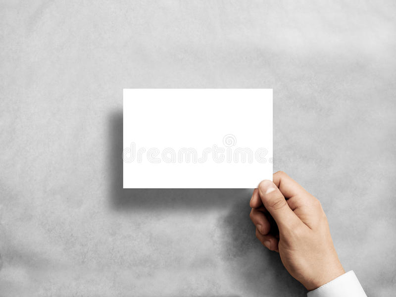 Hand holding blank white postcard flyer in the . stock photography