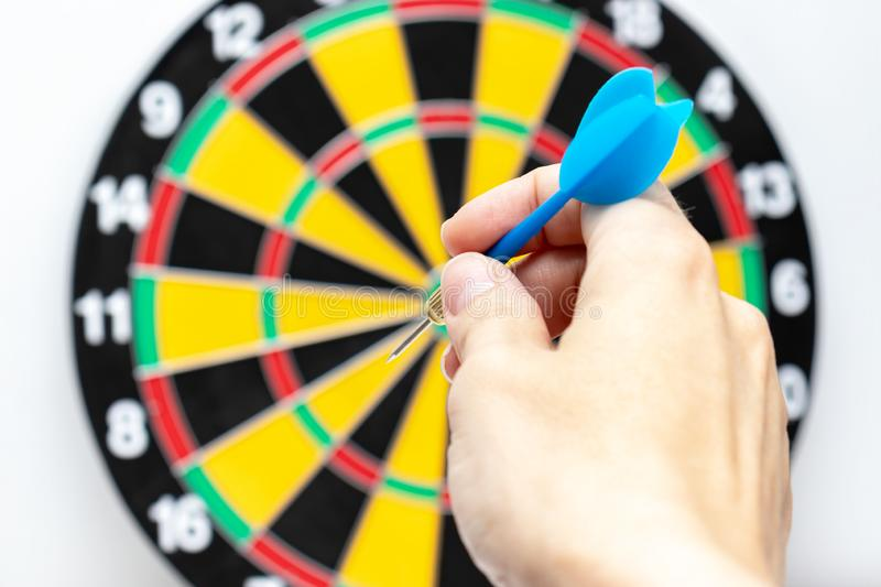 A hand holding a blue dart ready to throw it to a dartboard target, strategy and skill in business concept royalty free stock photos