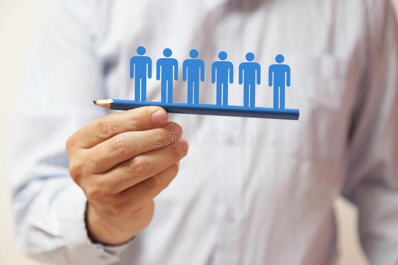 Hand holding a blue pencil with human figures royalty free stock image