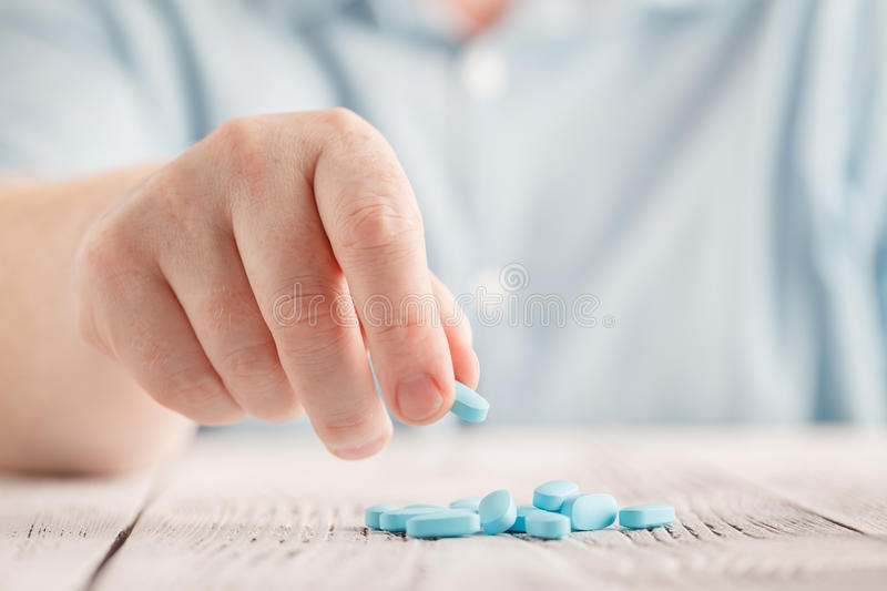 Hand holding a blue pill close up royalty free stock images