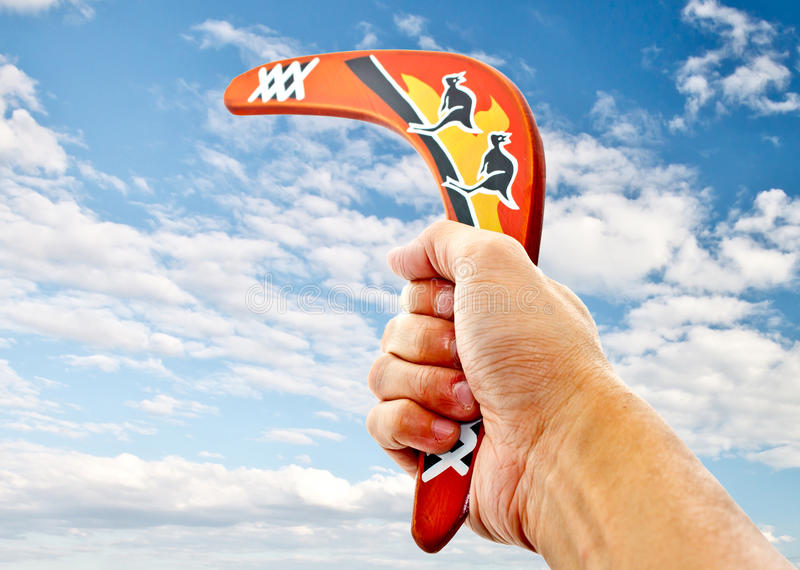 Hand holding a boomerang 1. Hand holding a boomerang pointing to blue sky stock image