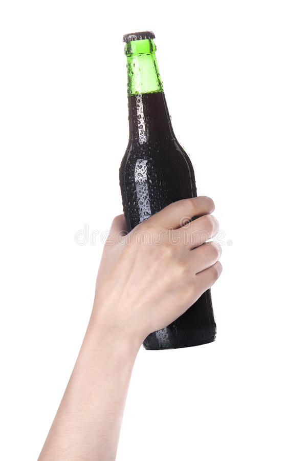 Hand holding Bottle of dark beer. With drops isolated on a white background stock images