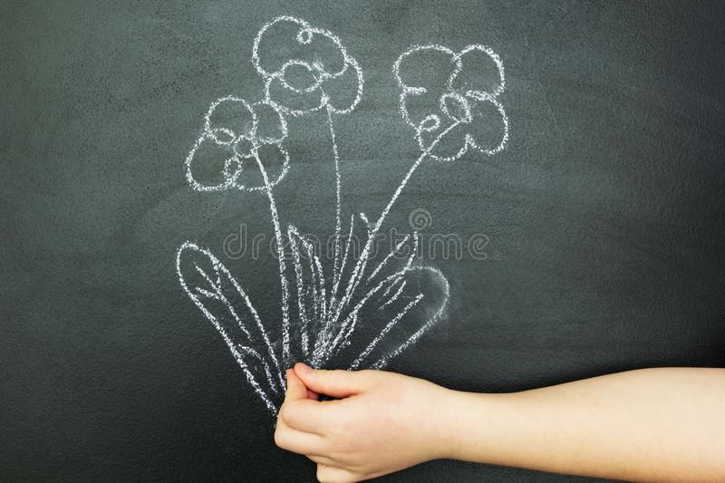The hand holding a bouquet of flowers to a black background stock illustration