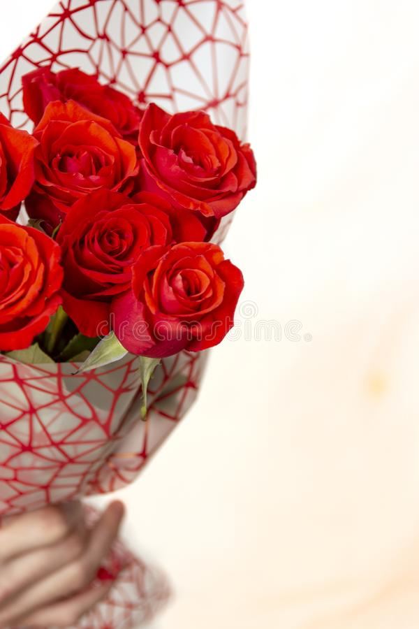 Hand holding bouquet of red roses over white background. Hand holding a bouquet of red roses on a white background. The concept of the celebration royalty free stock photo