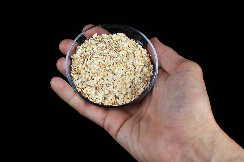 Hand holding the bowl of oatmeal flakes, against black background stock photos