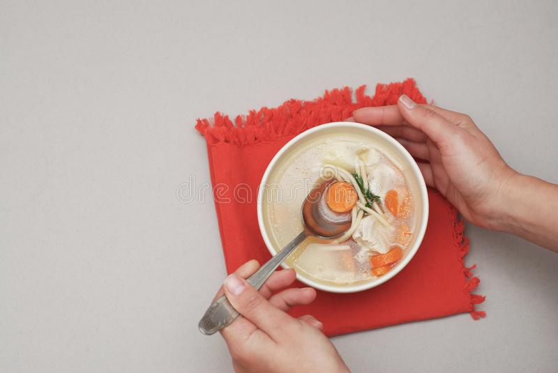 Hand holding a bowl with soup with on red napkin and gray background stock images