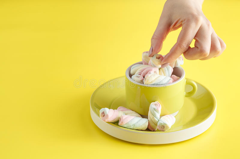 Hand holding bowl of sweet Marshmallow pastel isolated on yellow royalty free stock photo