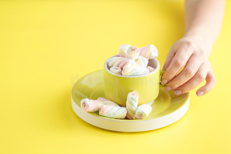 Hand holding bowl of sweet Marshmallow pastel isolated on yellow stock photography