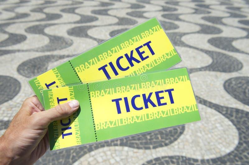 Hand Holding Brazil Tickets Copacabana Rio de Janeiro. Hand holding two Brazil tickets at the Copacabana Rio de Janeiro boardwalk royalty free stock photography
