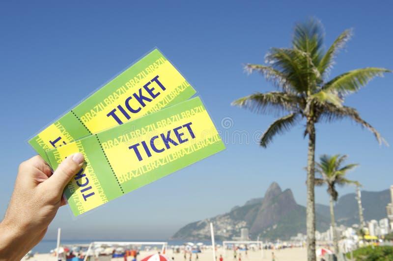 Hand Holding Brazil Tickets Palm Trees Rio de Janeiro. Hand holding pair of Brazil tickets in front of towering palm trees at Ipanema Beach Rio de Janeiro stock image