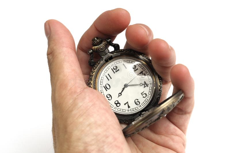 A hand holding a brown colored carved oriental pocket watch stock photography