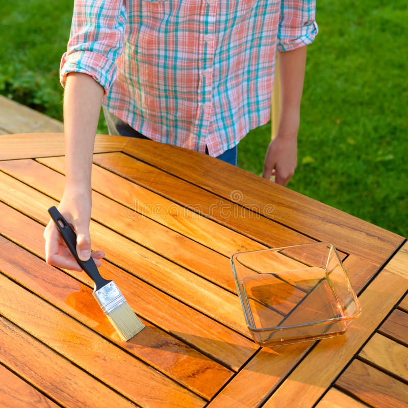 Download Hand Holding A Brush Applying Varnish Paint On A Wooden Garden  Table Stock Image
