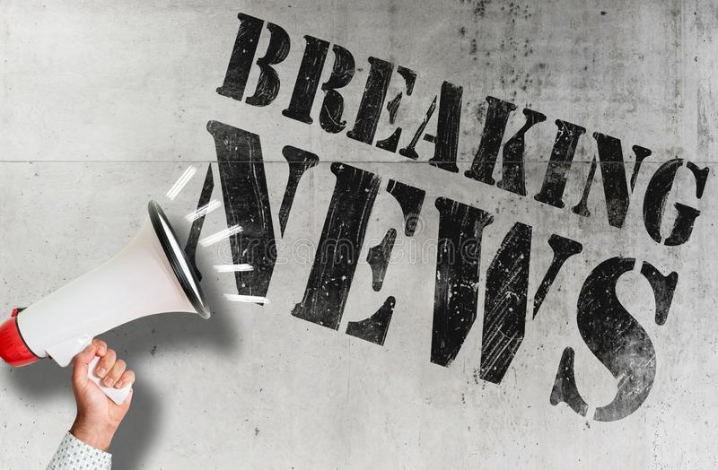 Hand holding bullhorn against concrete wall with text BREAKING NEWS. Hand holding megaphone against concrete wall with text BREAKING NEWS stock images