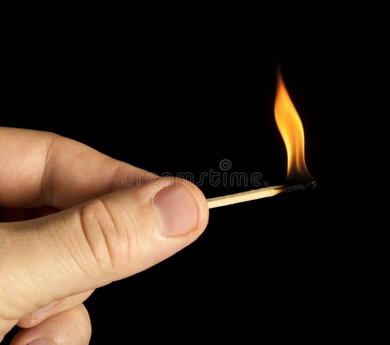 Hand holding burning match stick. Black isolated royalty free stock photo