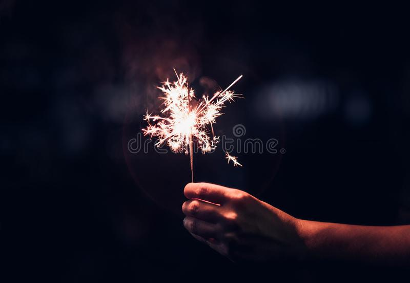 Hand holding burning Sparkler blast on a black background at night,holiday celebration event party,dark vintage tone. stock images
