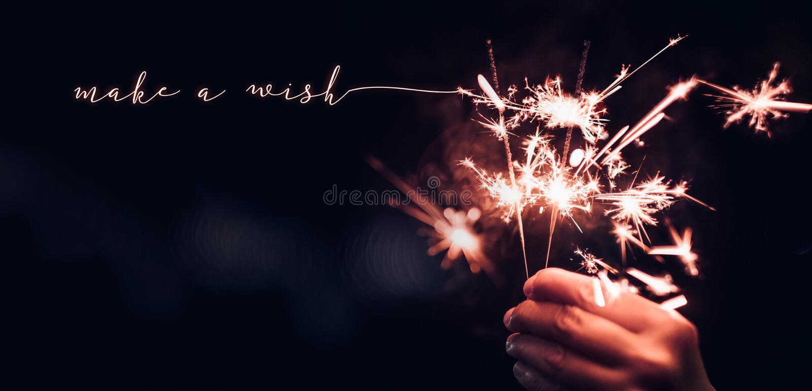Hand holding burning Sparkler blast with make a wish word on a b. Lack bokeh background at night,holiday celebration event party,dark vintage tone.copy space for stock photography