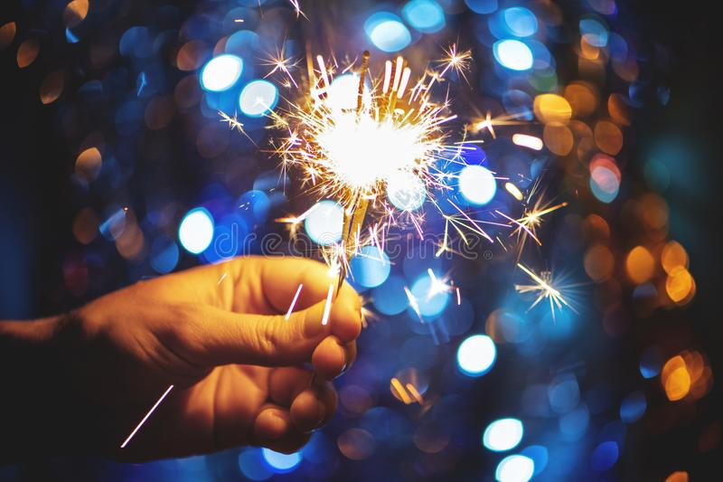 Hand holding a burning sparkler firework on Christmas light bokeh background. New Year and Christmas concept stock image