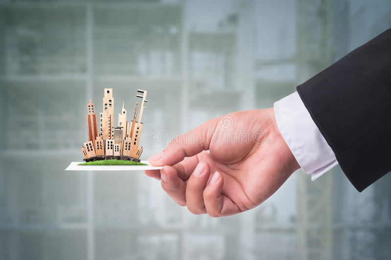 Hand holding business card with miniature building model. Real e. State concept royalty free stock photo