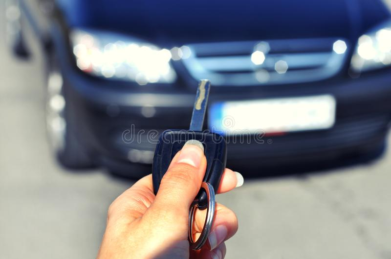 Hand holding button on the remote car. In selective focus of woman hand presses on the remote control car alarm systems. stock photo