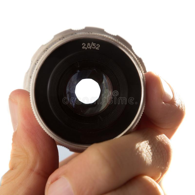 Hand holding camera lens on white background. Hand holding retro camera lens on white background royalty free stock photos