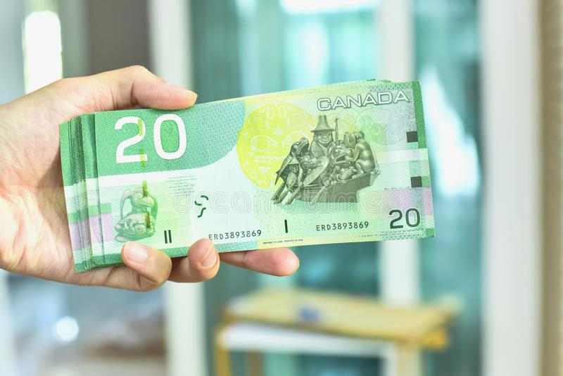 Hand Holding Canadian Twenty Dollar Banknotes. Close-Up View of Hand Holding Canadian Twenty Dollar Banknotes stock image