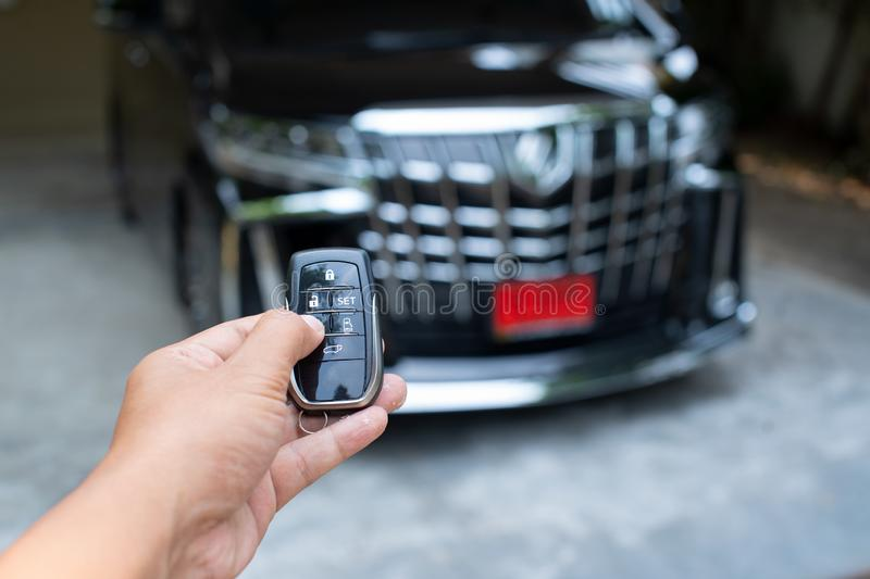 Hand holding car key ready to start a new car with blurred black car background.hand hold key blur car parking royalty free stock photos