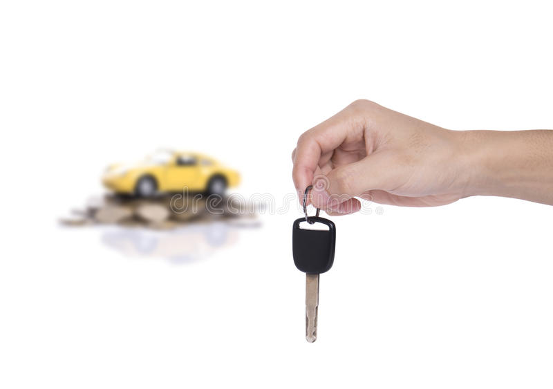Hand holding car key and yellow miniature car on a pile of stack. Coin isolated on white background royalty free stock photo