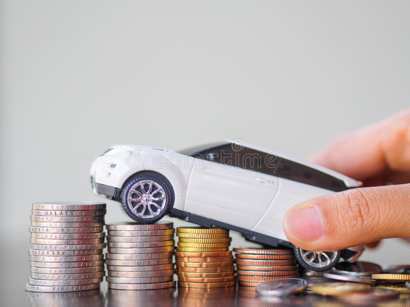 Hand holding car model on stack of coins. In business concept royalty free stock photography