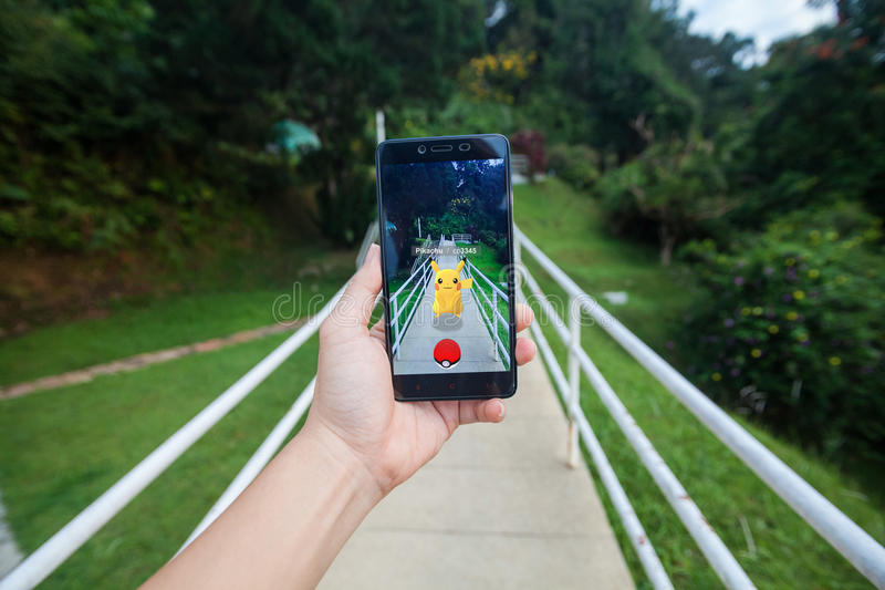 Hand holding a cellphone playing Pokemon Go royalty free stock image