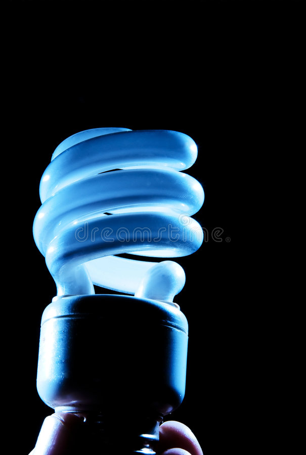 Hand holding cfl blue light-bulb lamp. A cfl light-bulb on black background being held by a human hand. blue hue on light stock photography