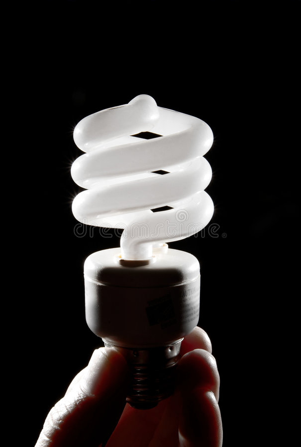 Hand holding cfl light-bulb lamp. A cfl light-bulb on black background being held by a human hand stock image