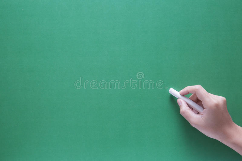 Hand holding chalk with green chalk board royalty free stock photo