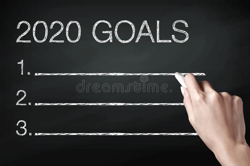 Hand holding a chalk and writing 2020 goals stock photo