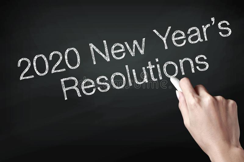 Hand holding a chalk and writing 2020 new year resolutions royalty free stock photography