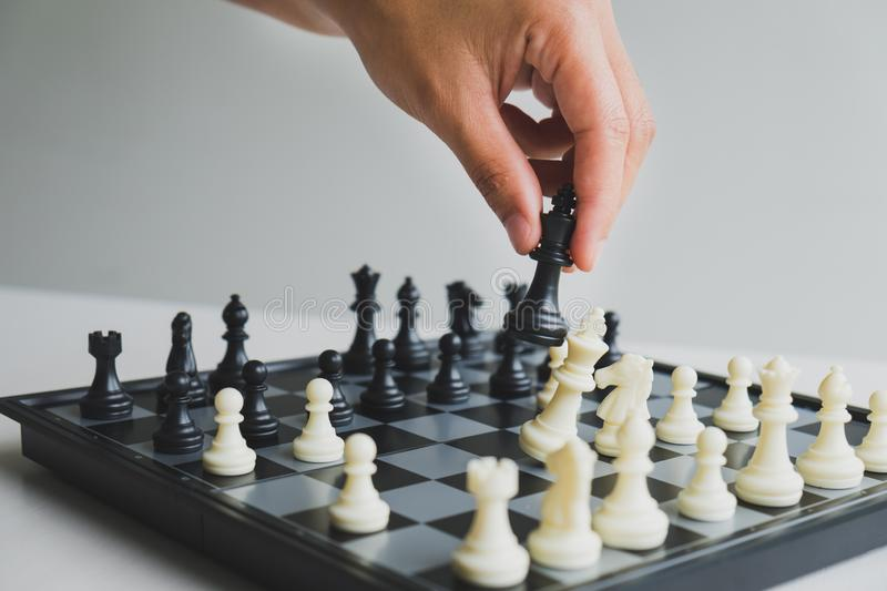 Hand holding chess pieces on board with white background, driven to success Business Strategy.  royalty free stock photo