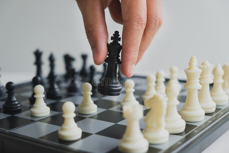 Hand holding chess pieces on board with white background, driven to success Business Strategy.  stock photos