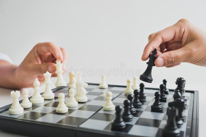 Hand holding chess pieces on board with white background, driven to success Business Strategy.  stock images
